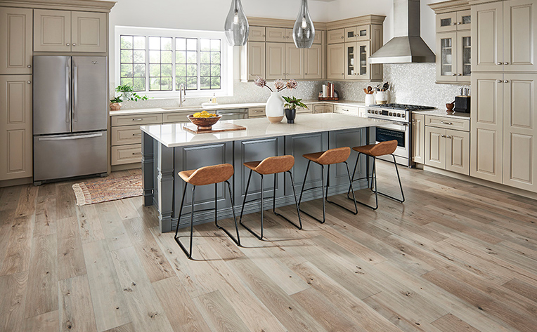 Modern and light colored open concept kitchen with wood look flooring
